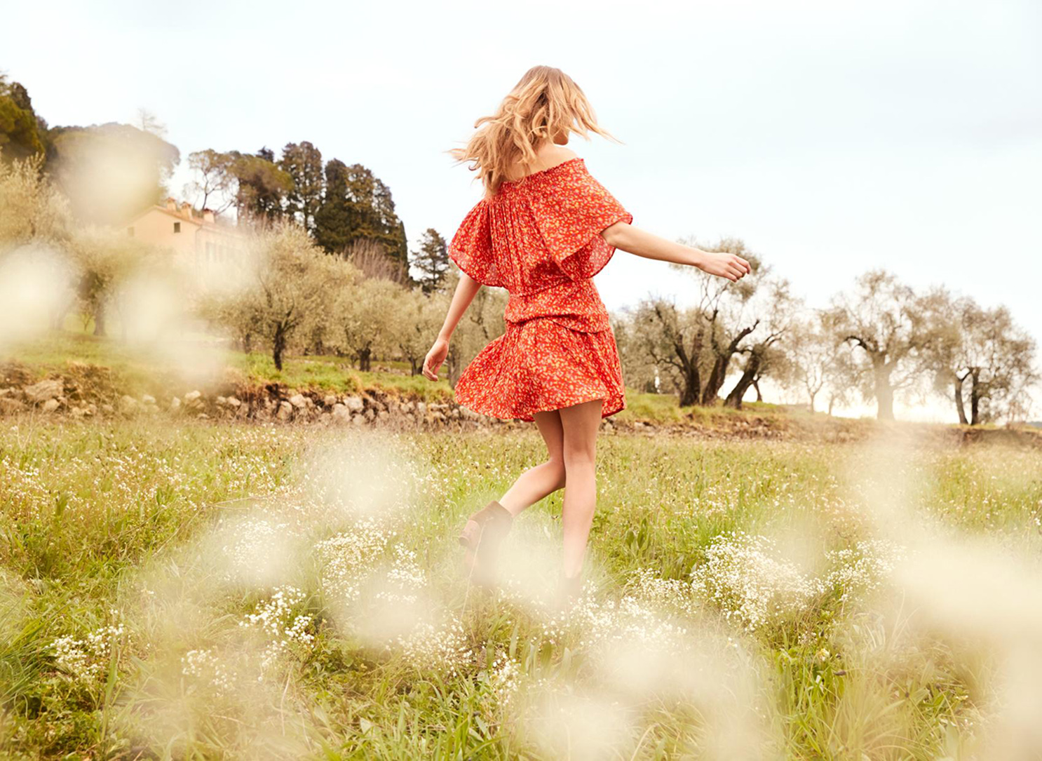 red dress walking field trees green blond hair