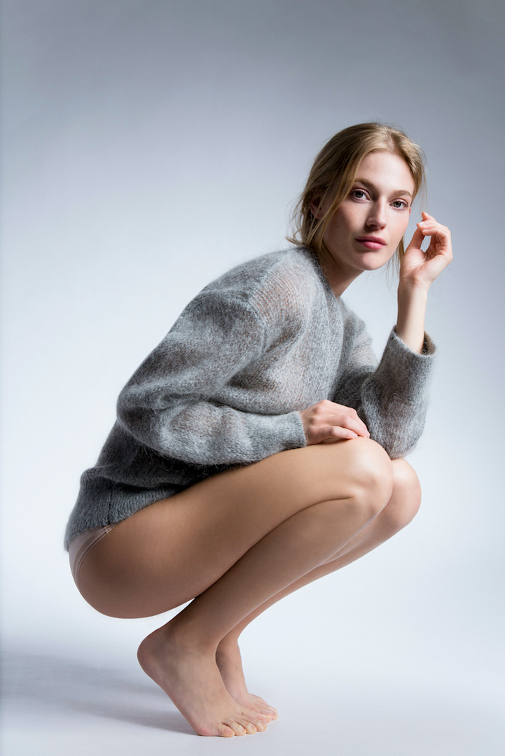 woman in grey pullover showing naked legs