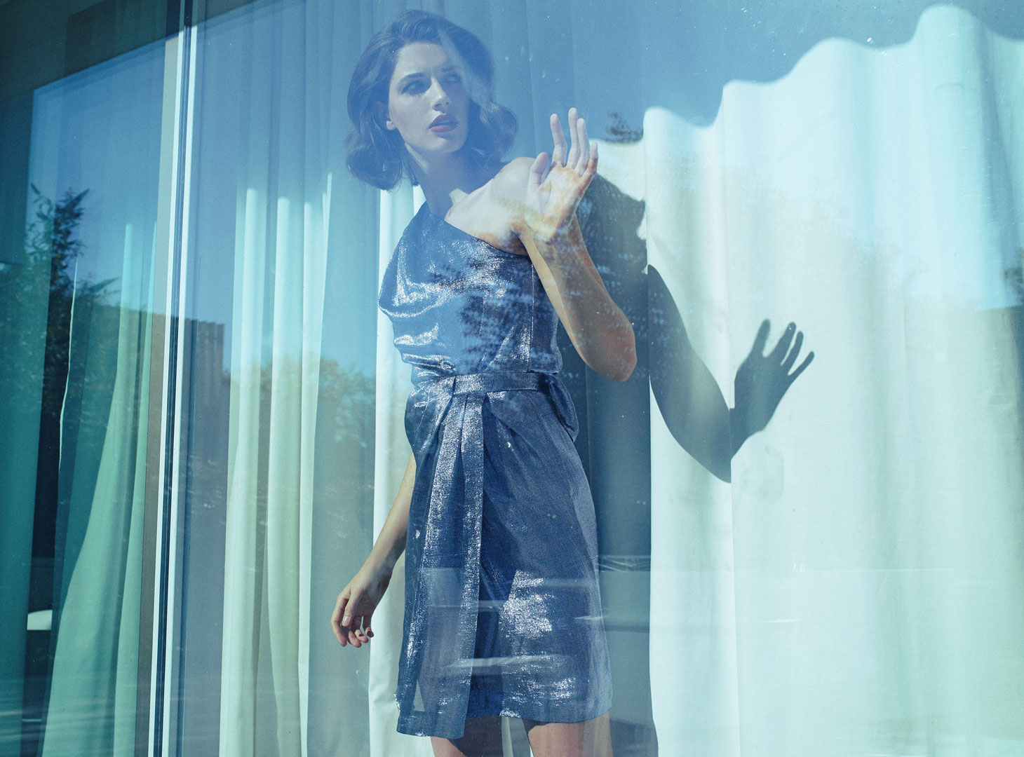 woman between curtains and window