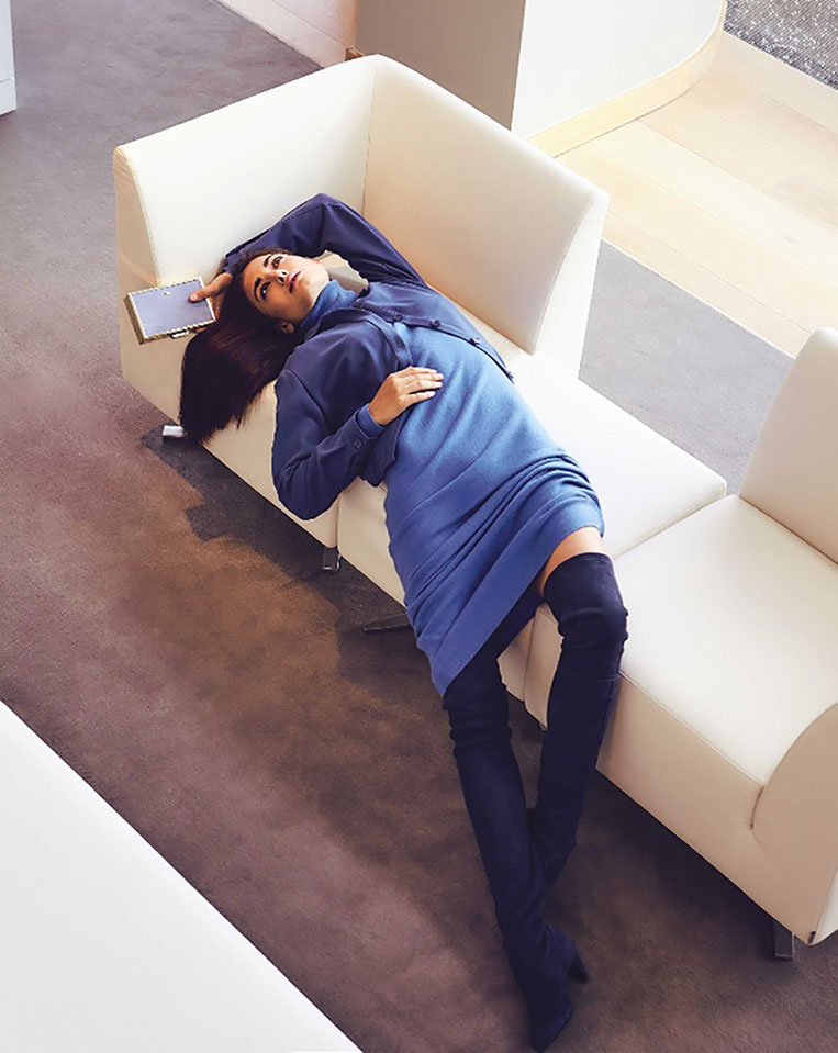 female model in blue lying in couch