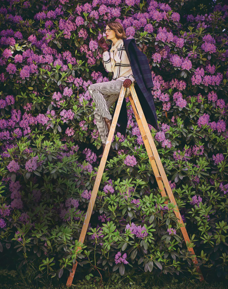 female model sitting on a ladder in front of a wall of flowers