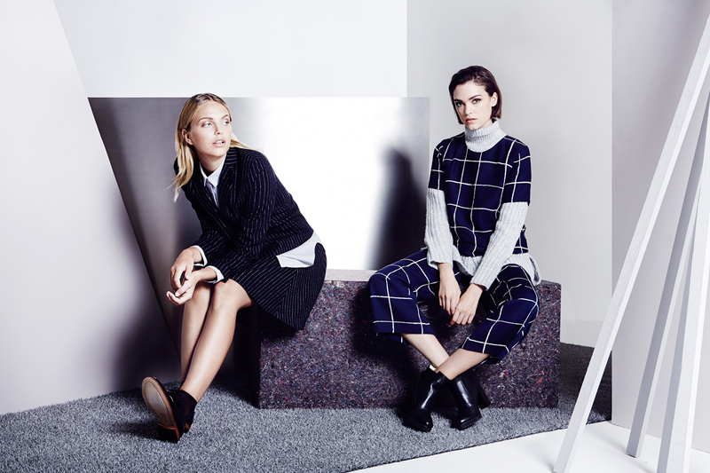 Two Models Sitting on Set Posing Minimal Grey Outfit
