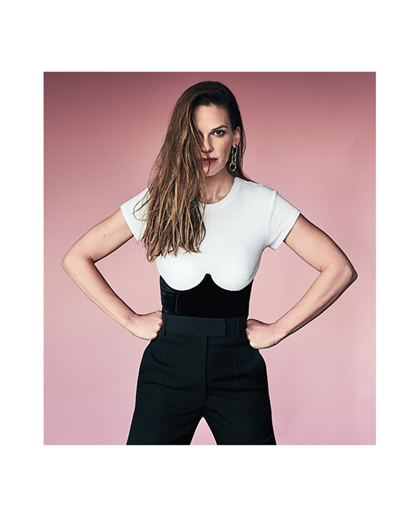 hilary swank purple wall white top black  tousers