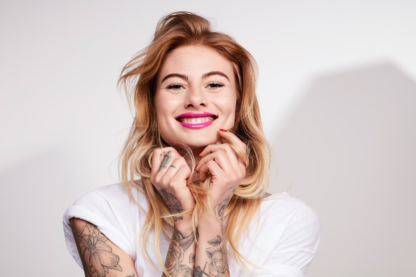 Tattoo Model Wavy Hair Brown Pink Lips Smiling