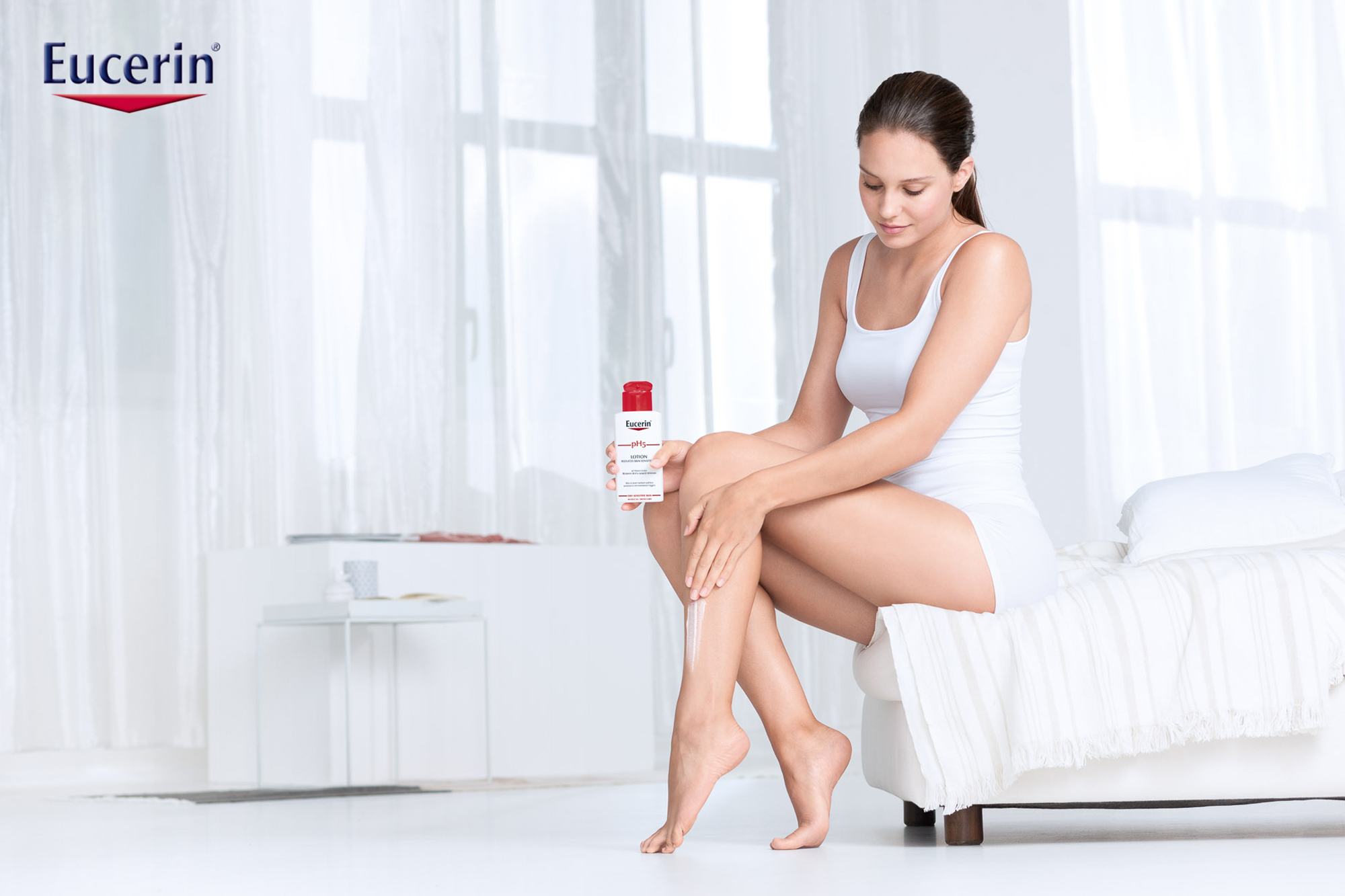 white room eucerin female model shirt dark hair creme legs