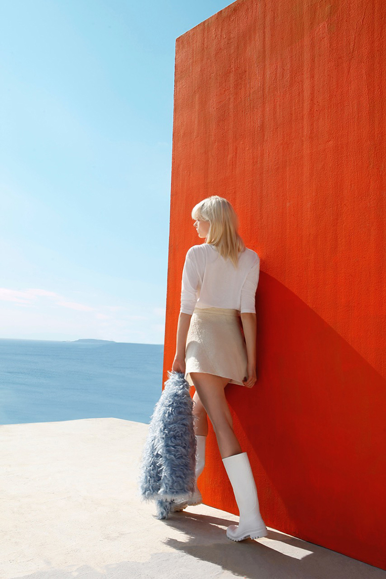 female model in sunlight standing infront of a red wall