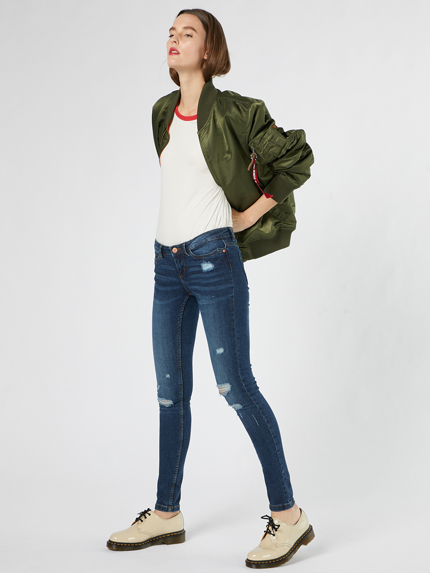 green jacket blue jeans woman standing