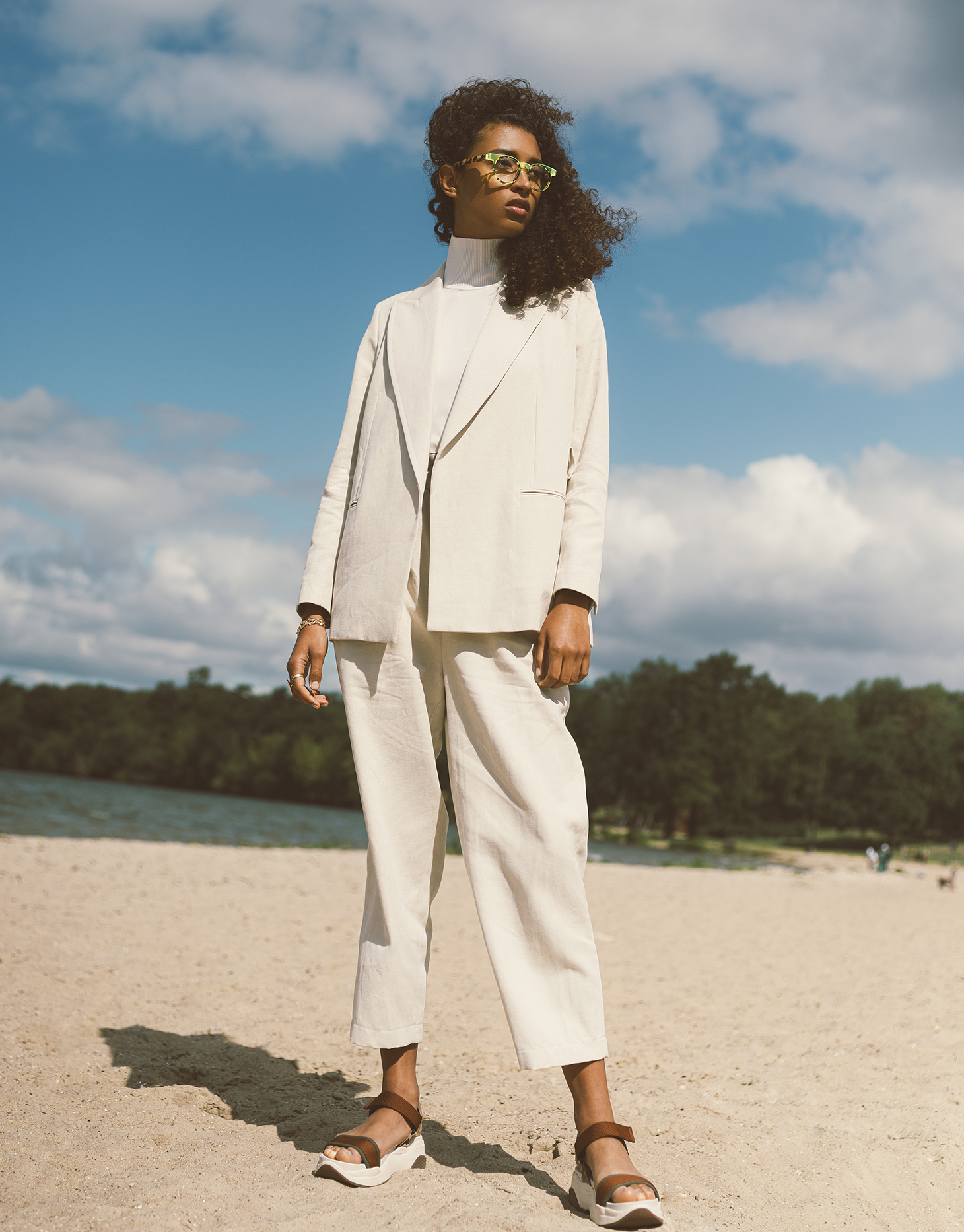 white suit curly hair beach bluey sky glasses